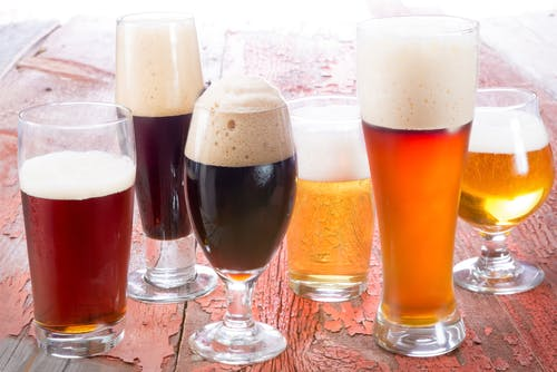 Image of different sized glassware holding beer varieties on a wood surface