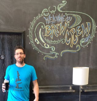 Image of Brew Crew's owner Brad McCauley wearing a blue t-shirt and holding a glass of beer standing in front of an image of Brew Crew's logo