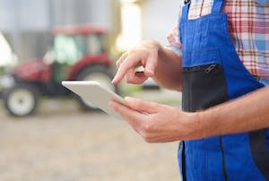Close-up photo of a farmer holding a tablet