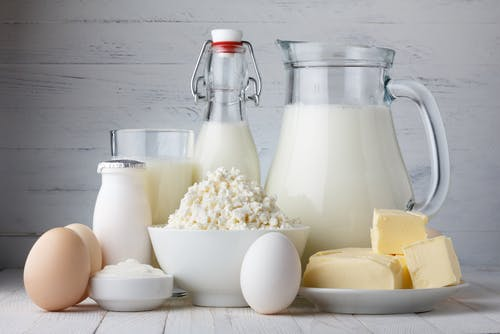 Image of processed dairy items on a wood background including milk and cheese.