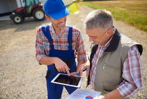 Photo of a farmer showing another farmer the display on a tablet