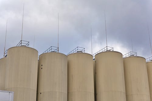 Photo of tan-colored silos against a cloudy sky outside of a brewery