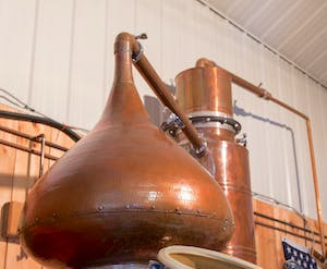 Photo of a copper distillation still inside of a distillery