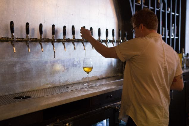 Image of Wassail server pouring cider at the bar with a row of tap handles in the background. Image courtesy of nyooberserver
