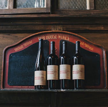 Photo of 4 red wine bottles lined-up in front of a red House Wines chalkboard sign at Brooklyn Winery. Photo courtesy of Clay Williams.