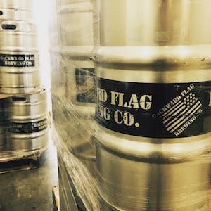 Photo of titanium kegs with black Backward Flag Brewing Co. labels on them