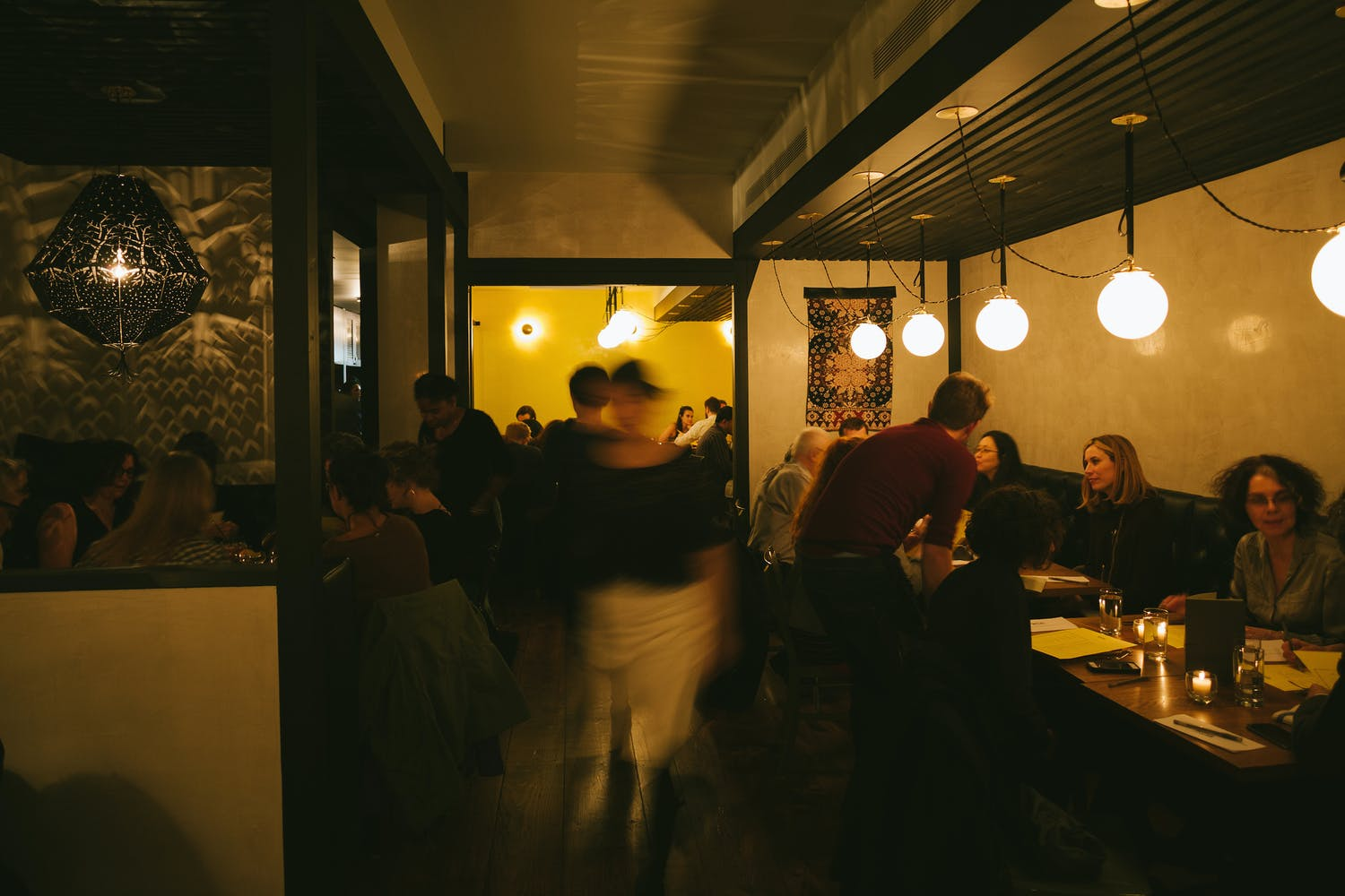 Image of the inside of Wassail cider bar in NYC, busy with guests and servers