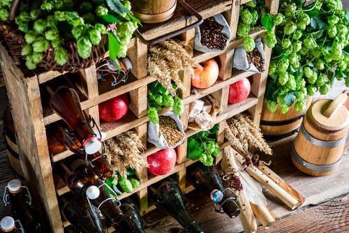 Photo of wooden cubby-holes filled with apples, dark brown glass bottles and other various types of fresh produce