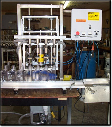 2 Head Bench Top Semi-automatic Overflow Filling Machine Bottle filler sold by Neumann Packaging