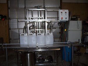 2 1/2 gallon Semi-automatic, 4 head, F-Style Overflow filling machine.